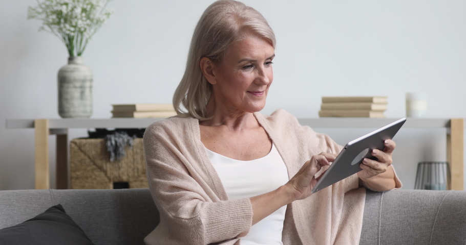 Smiling middle aged old woman relaxing holding digital tablet reading e book sit on sofa at home, senior adult lady enjoying using computer pad apps browsing internet shopping on couch in living room | Shutterstock HD Video #1037252573