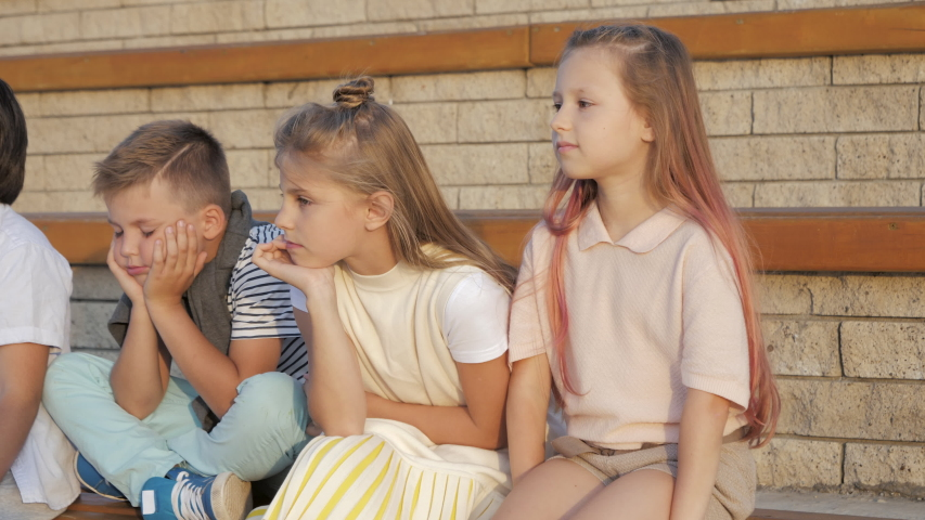 Tired and exhausted primary school kids sitting outdoors. | Shutterstock HD Video #1037264033