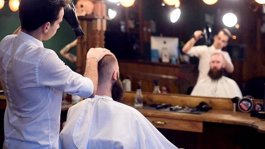 Male hairstyle and drying hair after haircutting in modern salon. Back view of barber styling hair with dryer. Finishing hairdressing service for bearded man. Copy space on blurred background | Shutterstock HD Video #1037268203
