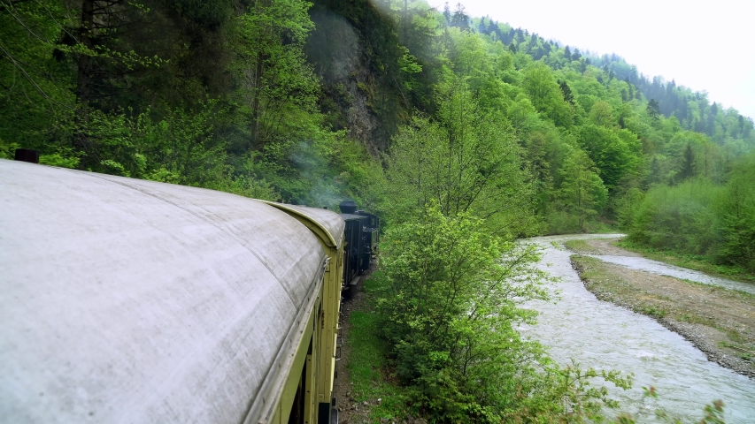View from the roof of a retro train wagon, Old steam locomotive in Romania, Steam narrow gauge train, Steam train chugging through the countryside, narrow-gauge railway