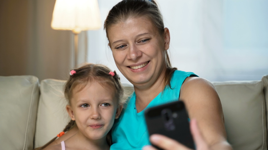 Little Girl Child With Mother Home On Sofa Using Smartphone   Shutterstock HD Video #1037314493