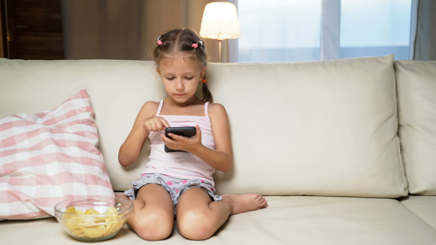 Little Girl Child Home On Sofa Playing On Smartphone   Shutterstock HD Video #1037314553
