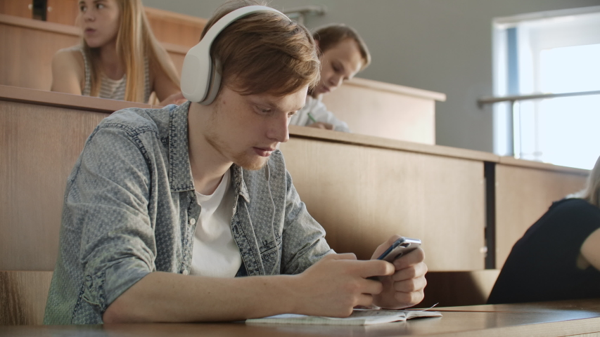 A student sitting in a university auditorium with a large group of people sits in headphones and listens to music and looks at the smartphone screen. It is in a state of calm. Class break.   Shutterstock HD Video #1037361263