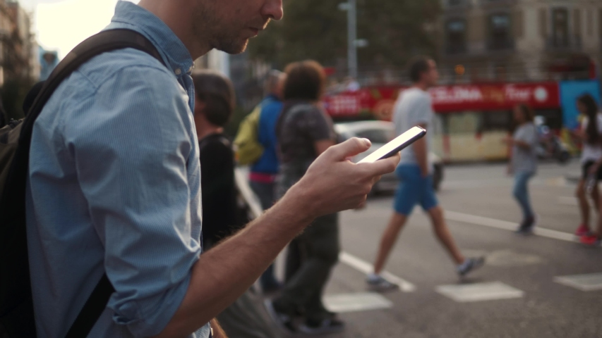 Man using touch Mobile Phone outdoor, close up, man walking with cell phone on city street people and cars background, crossroad use application | Shutterstock HD Video #1037365913