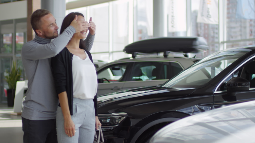 Cheerful man covering eyes of his wife for surprise in auto showroom and then taking hands off. Happy woman smiling and getting excited by new car as gift from loving husband | Shutterstock HD Video #1037418863