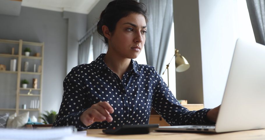 Serious young indian woman calculate domestic bills pay loan payment online on laptop sit at home office desk, focused businesswoman using computer calculator plan expenses manage finances concept   Shutterstock HD Video #1037437013
