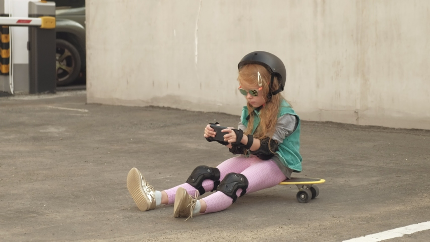 Cheerful Little girl with long red wavy hair in a helmet and protection on arms and legs sits on a yellow skateboard and uses a mobile phone. Internet surfing. Gray concrete wall in the background | Shutterstock HD Video #1037493083
