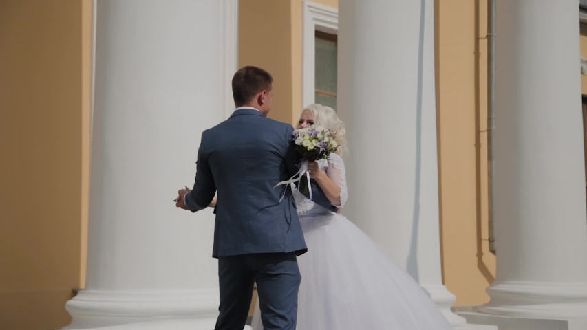 Happy newlyweds dance their dance at the columns in the park.   Shutterstock HD Video #1037609213