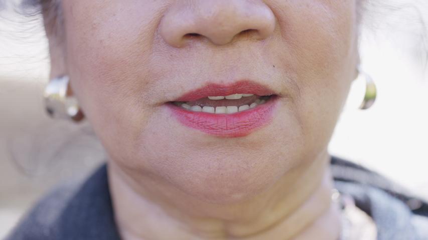 Close up of senior Filipino woman's mouth talking to camera  | Shutterstock HD Video #1037678483