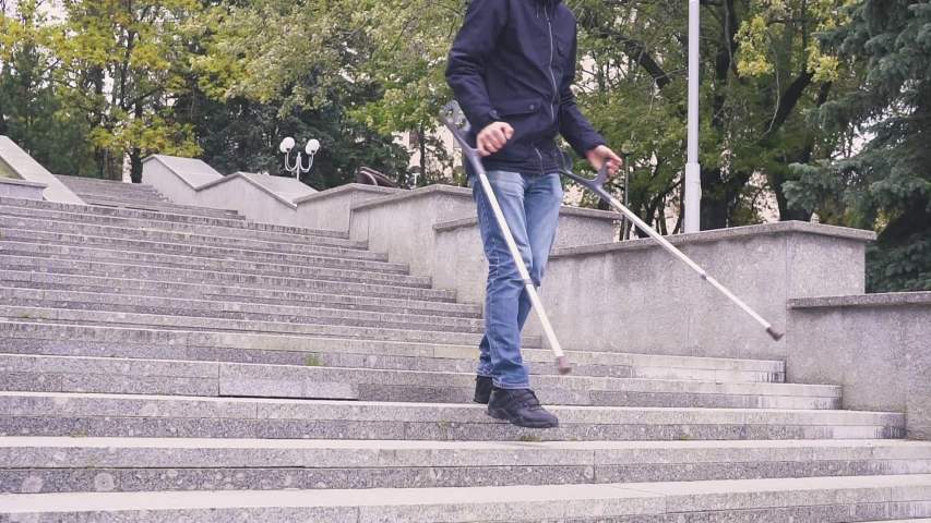 Man on crutches climbs a set of stairs. concrete staircase. Concept on an inclusive society and a barrier-free environment