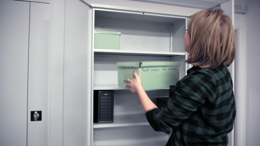 Woman inserting cardboard box into cabinet | Shutterstock HD Video #1037913743