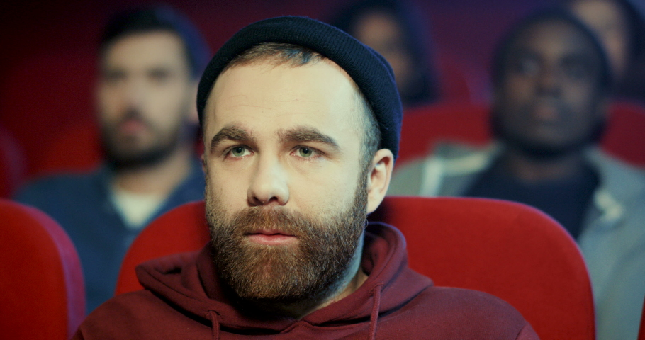 Close up of the young good looking hipster Caucasia man with a beard and in a hat watching an interesting movie in the cinema. | Shutterstock HD Video #1038178373