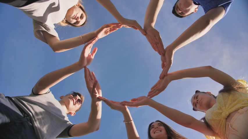 A group of friends makes a circle from the palms of their hands. | Shutterstock HD Video #1038199733