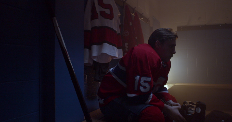 Hockey player sits in dramatically lit changer oom holding helmet with determination and focus in his eyes determined to win a crucial game in series. Puts on hockey equipment  | Shutterstock HD Video #1038217883