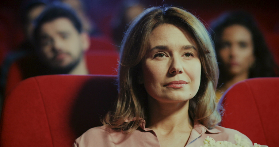 Portrait of the bored young Caucasian woman with fair hair watching boring, not interesting movie in the cinema. Close up. | Shutterstock HD Video #1038255623