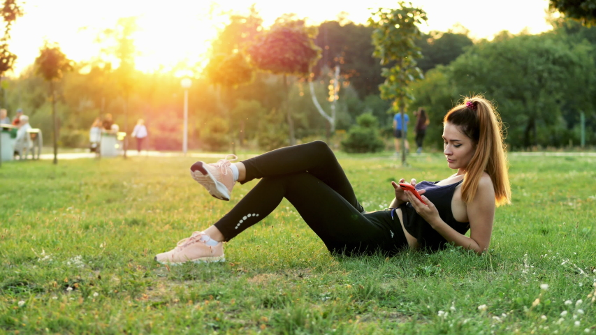 Sporty cute woman use mobile phone while lying on the grass in city park on sunset, have a break time during the training, use fitness app, people walking on background