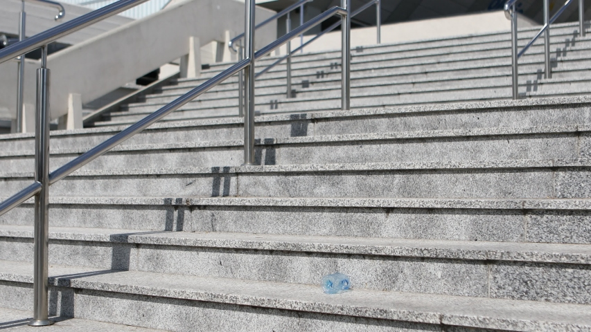 Woman in pink coat walks up the stairs, leans down and picks up a plastic bottle dropped down to the stairs. She is protecting the environment by keeping the cleanliness. Environmentally conscious act   Shutterstock HD Video #1038370523