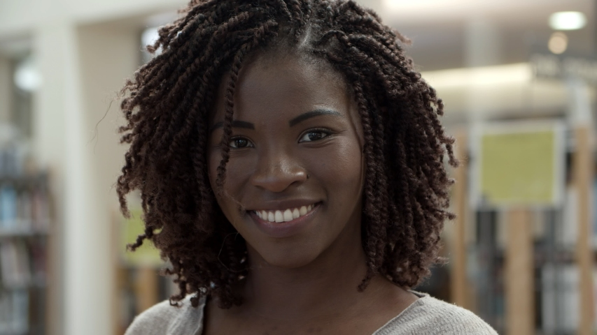 Closeup shot of smiling beautiful African American woman. Attractive young lady looking at camera. Female beauty concept #1038491633