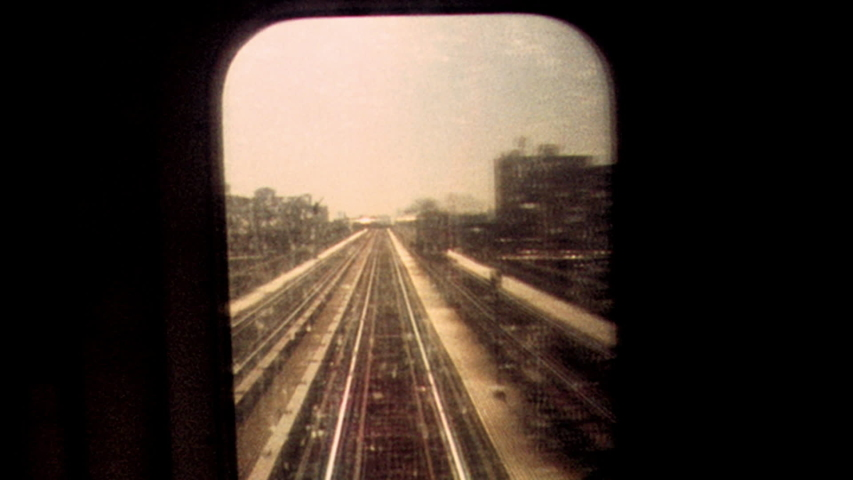 Retro looking archival footage filmed on New York City subway looking out through subway window at tracks and passing train as sun sets in the distance | Shutterstock HD Video #1038494243