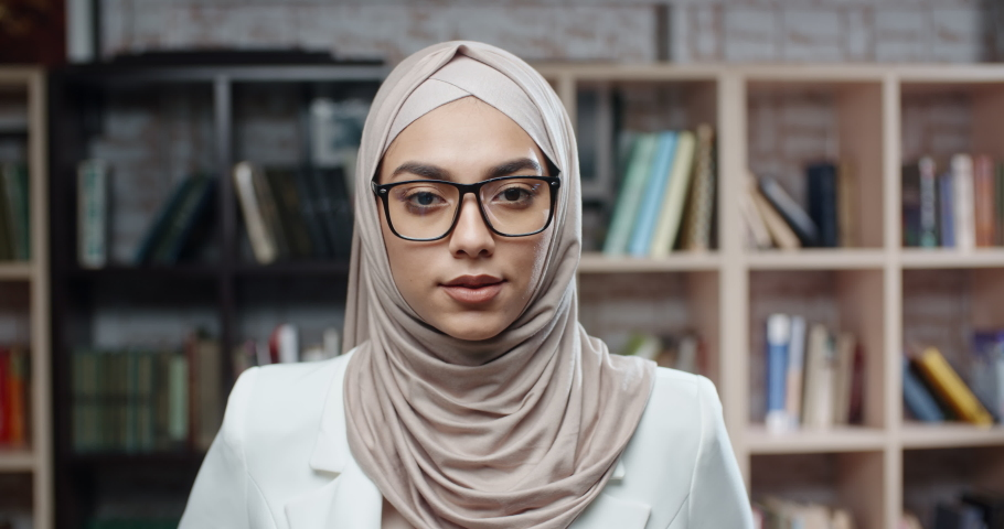 Female student wearing hijab confidently looking at camera. spending time in campus library studying - modern muslim concept close up 4k