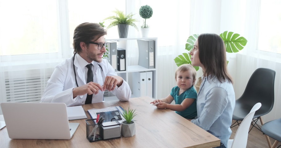 Doctor explaining mother with baby girl at clinic | Shutterstock HD Video #1038813533
