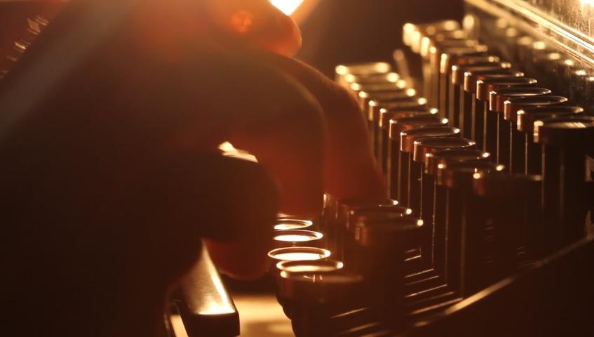 Close up shot of man typing on old vintage retro typewriter; backlit; news, media or communication concept | Shutterstock HD Video #1038918533