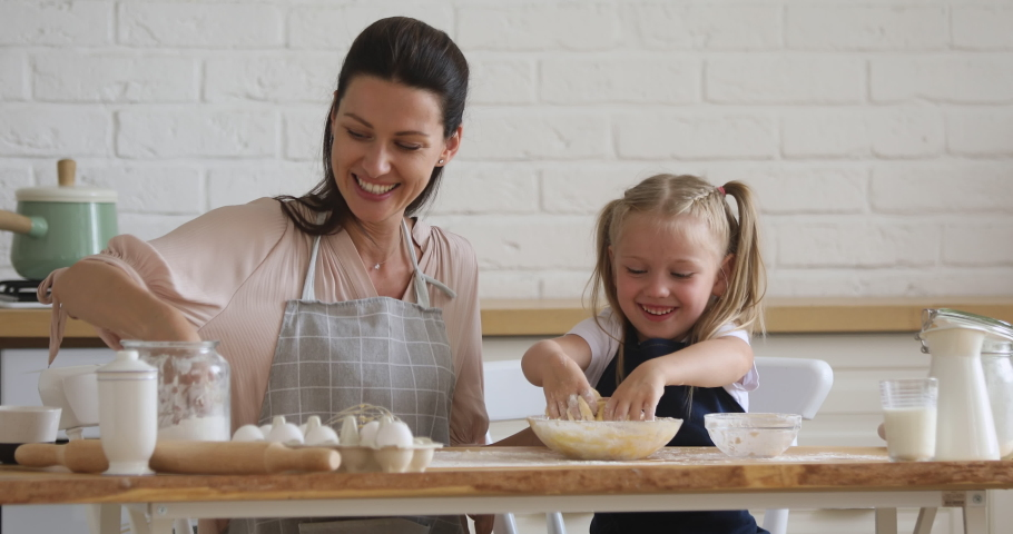 Cute small kid daughter learning kneading dough with hands helping mom in modern kitchen, happy family adult mother and little child girl prepare cookies biscuit having fun cooking together at home | Shutterstock HD Video #1038952463