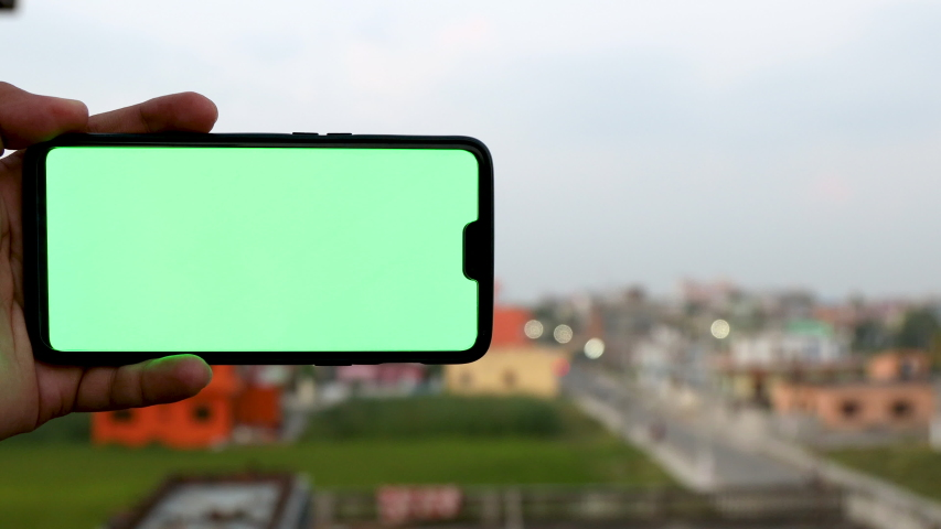 Panning shot of a man holding a smartphone with green screen  | Shutterstock HD Video #1039008383