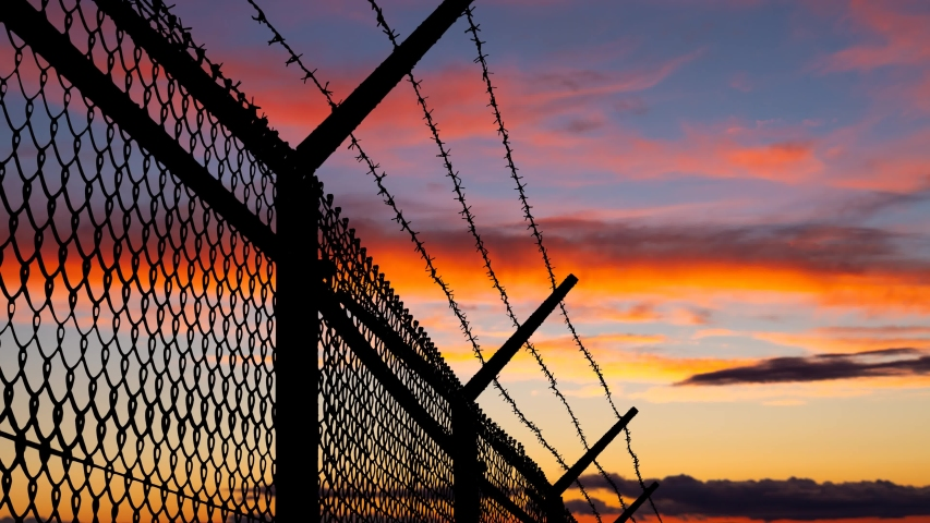 Wired Fence with Barbed Wire and Mesh Steel Wall at Twilight, Concept of Prison, Salvation, Refugee, Isolation, Loneliness | Shutterstock HD Video #1039082933