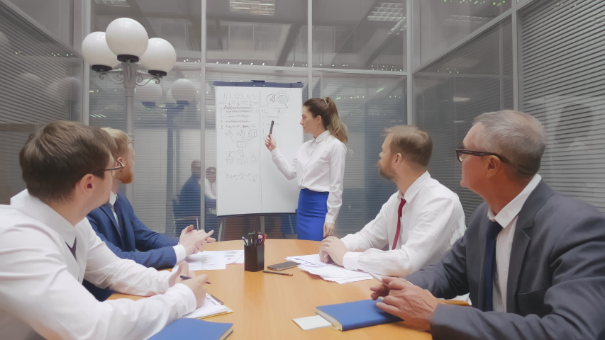 Company head and business trainer stands in front of audience diverse staff members making presentation using flip chart raised sales positive results of work done, seminar corporate education concept   Shutterstock HD Video #1039133933