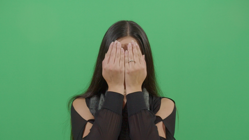 Hands Covering The Face Of A Woman In The Sense That Something Bad Happened Or Can Not Look At The Viewer. Studio Isolated Shot Against Green Screen Background | Shutterstock HD Video #1039151033