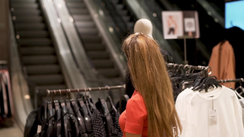 Close-up shopper girl pulls out a fashionable chiffon black dress with white polka dots from a hanger in a fashion store boutique shopping Mall, slow motion, Elevator in the background, buying selling | Shutterstock HD Video #1039187273