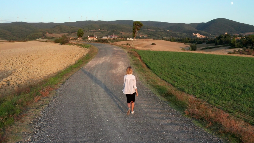 Beautiful young woman walking on a country road   Shutterstock HD Video #1039187873
