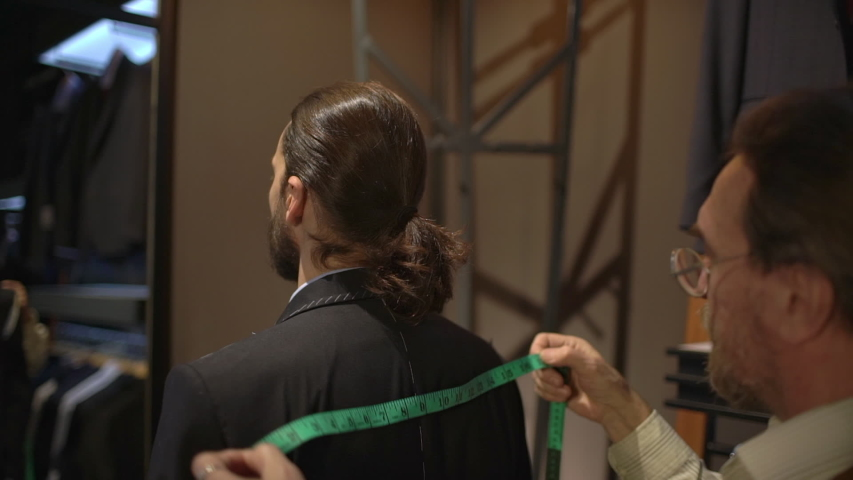 Slow motion rear view of serious-looking businessman fitting handmade jacket, looking mirror while tailor finish taking measures of back with measure tape, sew suit in atelier. Fashion concept | Shutterstock HD Video #1039192313