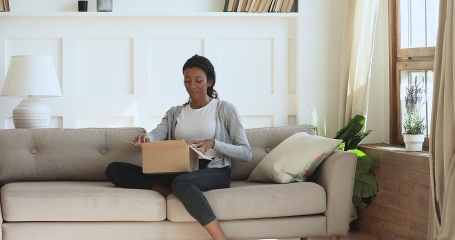 Curious happy young african woman customer holding opening parcel sit on sofa in living room, surprised lady consumer receive post shipment online shop sale order satisfied with fast delivery concept | Shutterstock HD Video #1039317683