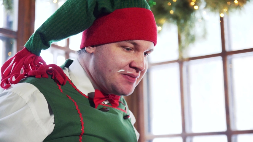 Funny elf with dirty face eats quickly. Hungry male elf in red and green hat eats and drinks indoors. Close-up. | Shutterstock HD Video #1039326173