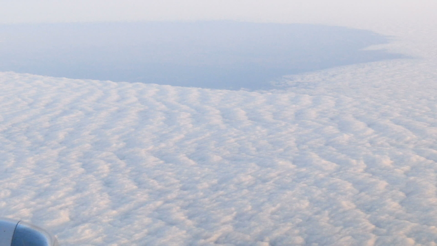 Beautiful cloudy sky from aerial view. Sunrise clouds from airplane window  | Shutterstock HD Video #1039411223