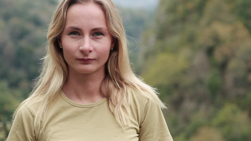 Beautiful smiling girl in fingers up. Happy young woman on a background of mountains | Shutterstock HD Video #1039431953