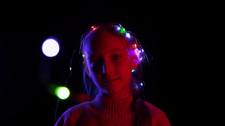 Content girl talking and playing with Christmas garland wreath flashing. Adorable teenage girl with illuminated colorful xmas garland on hand smiling at camera in darkness #1039861373