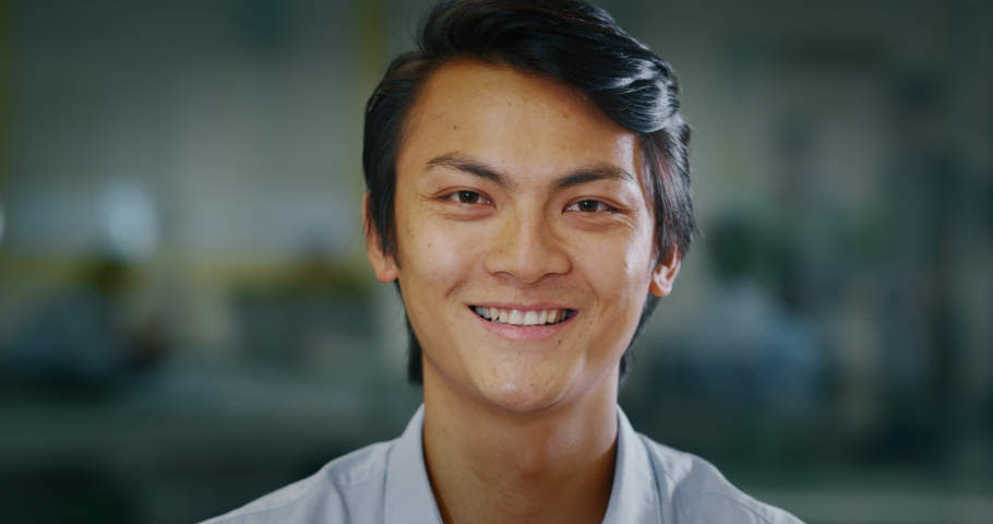 Portrait of an young successful asian businessman is smiling satisfied with his work in camera in an office.