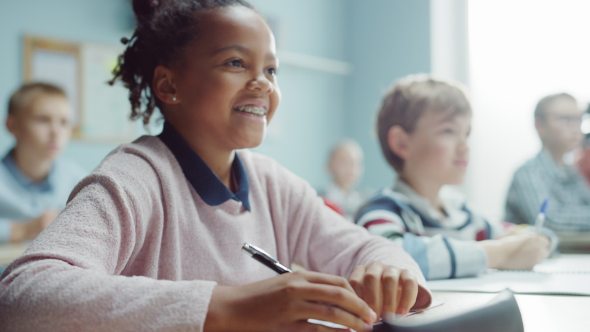 In Elementary School Class: Portrait of a Brilliant and Cute Black Girl with Braces Writes in Exercise Notebook, Smiles. Junior Classroom with Diverse Group of Bright Children Working Diligently | Shutterstock HD Video #1040038283