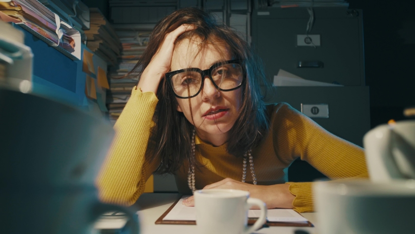 Stressed businesswoman working late at night in the office, she had too many cups of coffee and feels exhausted
