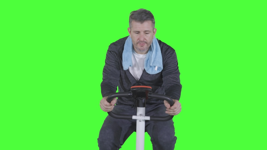 Unhappy caucasian man looks lazy to exercise on the exercise bike. Shot in 4k resolution | Shutterstock HD Video #1040209583