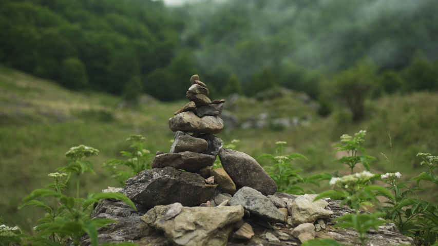 Female Explorer redhead woman putting a pebble on Hiker Cairn then walking, hiking in french mountain, in nature, black backpack, green trees forest, mountains during summer in France. 4K UHD. | Shutterstock HD Video #1040270453