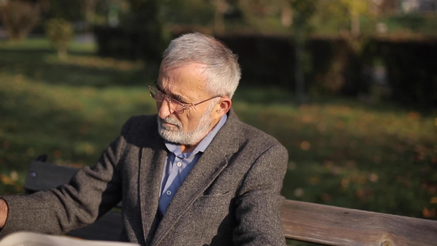 Handsome grandfather with a beautiful beard in a gray jacket sits on a bench in the park and reads a newspaper. Senior gray-haired man in glasses | Shutterstock HD Video #1040353103