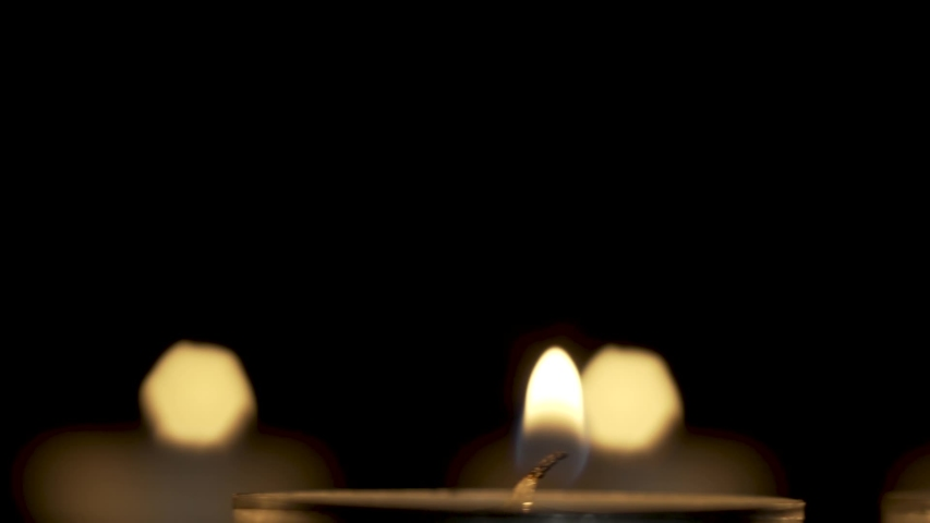 Lit candles slowly ride in a circle in the dark, the camera slowly zooms in   Shutterstock HD Video #1040477003