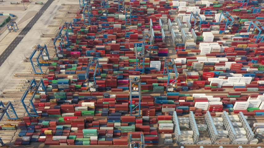QINGDAO, CHINA – SEPTEMBER 2019: Tilted aerial view of colorful cargo containers stacked in the Port of Qingdao, industry shipping globalization transportation infrastructure China Asia | Shutterstock HD Video #1040553473