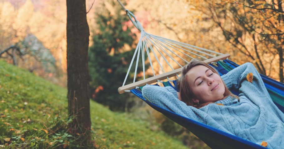 Woman Sleeps in a Hammock in Autumn. SLOW MOTION. Young woman daydreams, unwinds in a calm fall outdoor, rural country nature with colourful forest in background. Cozy morning or evening. | Shutterstock HD Video #1040588243