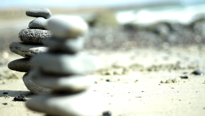 Zen stones on a beach, dolly shot