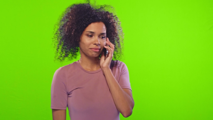 People, technology and lifestyle concept. Happy hipster dark-skinned girl talking on the mobile phone, smiling, receiving good news, gestures actively from happiness over chroma key background | Shutterstock HD Video #1040707523